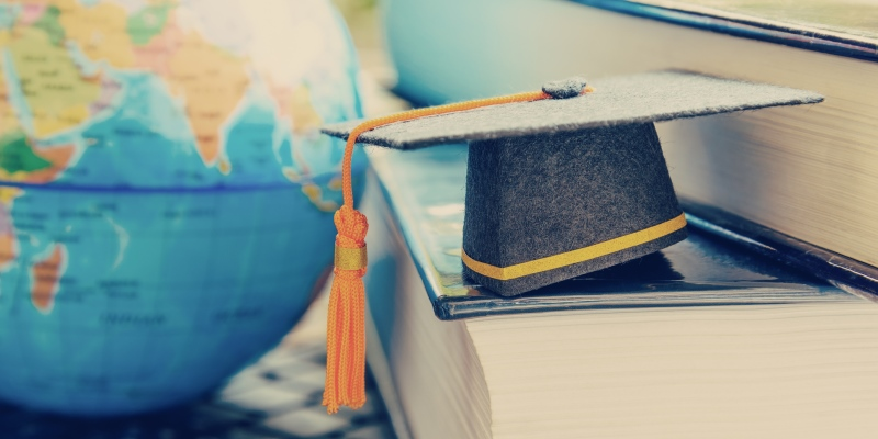 Graduate study abroad program for opening or expand world view concept Graduation cap or hat, world globe map and foreign book on a laptop, depicts an achievement or success in long distant learning