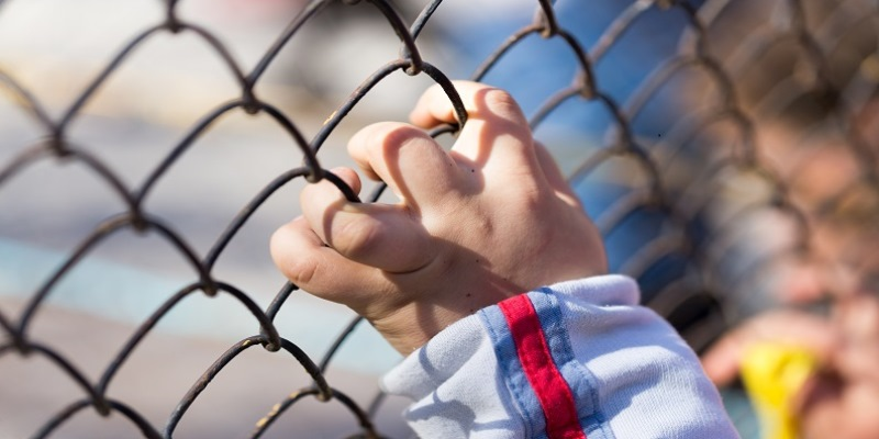 Child's hand on a grid of a metal fence