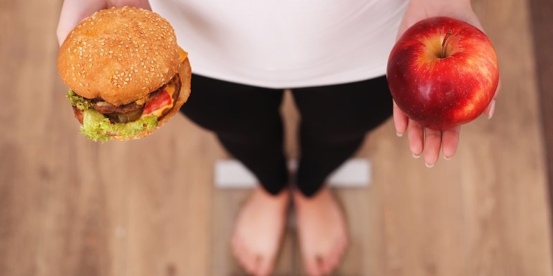 Diet. Woman Measuring Body Weight On Weighing Scale Holding Burger and apple. Sweets Are Unhealthy Junk Food. Dieting, Healthy Eating, Lifestyle. Weight Loss. Obesity. Top View