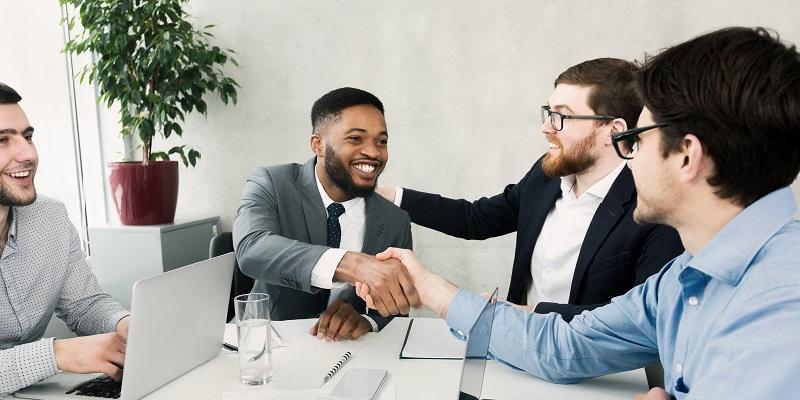 Happy team congratulating successful worker by shaking hands, having meeting in office