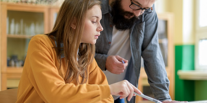 Young teacher helping his student in chemistry class. Education, Tutoring and Encouragement concept.