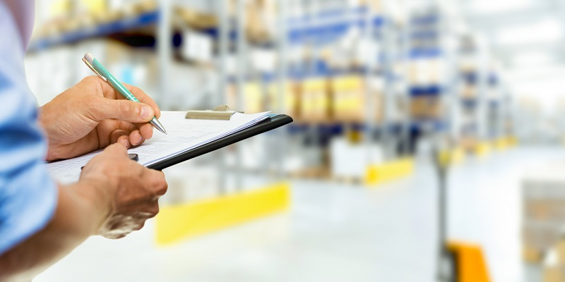 logistics service man writing documents on clipboard in warehouse