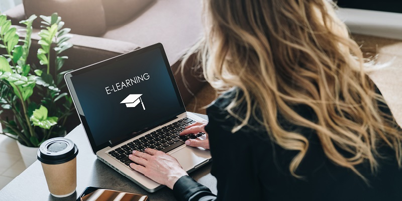 Rear view. Young woman, girl, student is sitting at table, working on laptop with inscription on screen e-learning and image of square academic cap. Online education,e-learning, distance training.