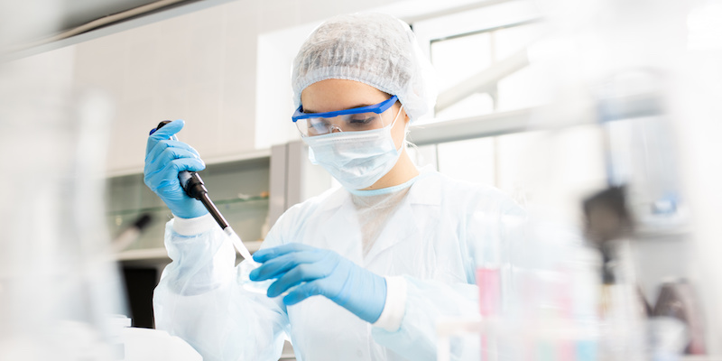 Serious concentrated female microbiologist in sterile clothing and safety goggles sitting at table and dropping reagent in petri dish while doing research in laboratory